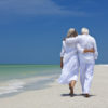 A senior couple with their arms wrapped around one another walks along a sandy tropical beach.  They are both wearing all white, with the exception of their footwear. In the background, a clear blue sky provides contrast to the all-white attire.  The tide flows on the shore, nearly touching the couple's feet.
