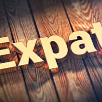 "The word ""Expat"" is lined with gold letters on wooden planks. 3D illustration pic"