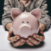 Close-up shot of elderly woman holding pink pig money-box. Senior woman hands holding a piggybank. Concept of saving money for old age.