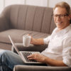Being a freelancer. Joyful handsome positive man using the laptop and enjoying his tea while working at home