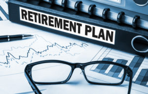Retirement plan with graphs and glasses on desk